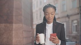 Portrait of a young African American businesswoman in a suit, walking around the city, drinking coffee and using. Smartphone. Female professional in suit having stock video footage