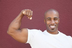 Portrait of a young African American man flexing muscles over colored background Royalty Free Stock Image