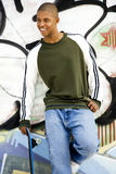 Portrait of a young African American man in front of a graffiti covered wall Stock Photos