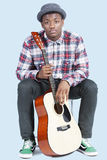 Portrait of a young African American man with guitar over light blue background Stock Images