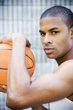 Portrait of a young African American man holding a basketball. Stock Photos