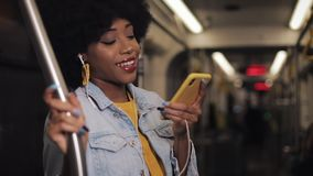 Portrait of young african american woman with headphones listening to music, sing and funny dancing in public transport