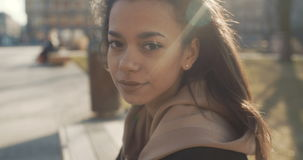 Portrait of young African American woman looking to a camera, outdoors. Slow motion. stock footage