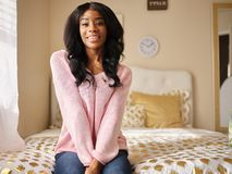 Portrait of young african american woman sitting on bed smiling royalty free stock photos