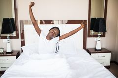 Portrait of young African American woman stretching after wake up in bed at home. Portrait of young African American woman stretching in bed at home royalty free stock images