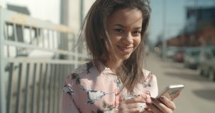 Portrait of young African American woman using phone.