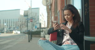 Portrait of young African American woman using phone at cafe. Beautiful young woman typing on phone, outdoors stock video