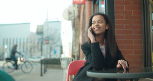 Portrait of young African American woman using phone, outdoors. Beautiful young woman talking on phone at restaurant cafe during sunny day Royalty Free Stock Images