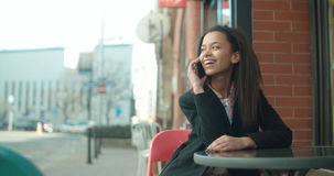 Portrait of young African American woman using phone, outdoors. Beautiful young woman talking on phone at restaurant cafe during sunny day Royalty Free Stock Photography