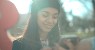 Portrait of young African American woman using phone, outdoors. Beautiful young woman typing on phone during sunny day Royalty Free Stock Images