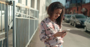 Portrait of young African American woman using phone, outdoors. Portrait of a young African American woman wearing bomber jacket texting on phone, outdoors Royalty Free Stock Photography