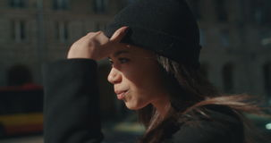 Portrait of a young African American woman waiting for a taxi or bus, outdoors. stock video footage