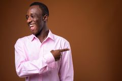 Portrait of young African businessman laughing and pointing finger royalty free stock photography