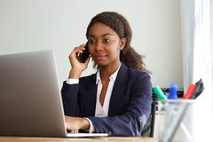 Young african businesswoman working on laptop and making phone call. Portrait of young african businesswoman working on laptop and making phone call Stock Photography