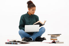 Portrait of young african girl with laptop over white background. Portrait of young beautiful african girl with laptop and books reading over white background Royalty Free Stock Images