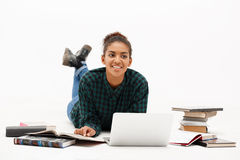 Portrait of young african girl with laptop over white background. Portrait of young beautiful african girl with laptop and books smiling over white background Stock Photo