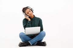 Portrait of young african girl with laptop over white background. Portrait of young beautiful african girl in headphones with laptop listening music, smiling Stock Images