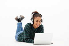 Portrait of young african girl with laptop over white background. Portrait of young beautiful african girl in headphones with laptop looking at screen, smiling Stock Photography