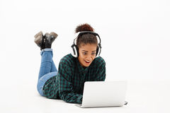 Portrait of young african girl with laptop over white background. Portrait of young beautiful african girl in headphones with laptop looking at screen, smiling stock photos