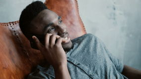 Portrait of young African male with a beard sitting in chair, using his Smartphone. Man talks on phone and smiles. stock video footage