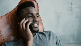 Portrait of young African male sitting in the chair and talking on Smartphone. Man laughs and nods his head agreeing. Portrait of young African male with a Royalty Free Stock Photography