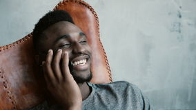 Portrait of young African male sitting in the chair and talking on Smartphone. Man laughs and nods his head agreeing. Portrait of young African male with a Stock Image