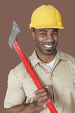 Portrait of young African man holding axe on shoulder over colored background Royalty Free Stock Photography