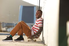 Young african man sitting over skateboard and smiling Royalty Free Stock Photo