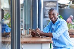 Smiling African man working online at a sidewalk cafe counter. Portrait of a young African man smiling while sitting outside at a counter of a sidewalk cafe Royalty Free Stock Images