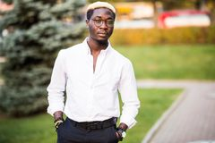 Portrait of handsome african man in white shirt style clothes on the city street. Portrait of young african man in white shirt style clothes on the city street Royalty Free Stock Photography