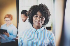 Portrait of young african woman with afro looking and smiling at the camera.Business team on background in modern office Stock Image