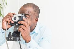 Portrait of a young afro american man taking pictures on an old vintage camera stock image