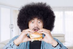 Young man eating a big cheeseburger. Portrait of young Afro man looks excited while eating a big cheeseburger in the living room Royalty Free Stock Image