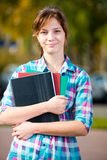 Portrait of young alluring woman holding education books. Student girl. Royalty Free Stock Image