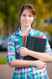 Portrait of young alluring woman holding education books. Student girl. Portrait of young alluring woman holding education books. Standing at summer college Stock Photos
