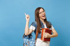 Portrait of young amazed amused woman student in glasses with backpack holding books, pointing index finger up on copy. Space isolated on blue background stock images