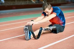 Handicapped Sportsman Stretching in Stadium stock images