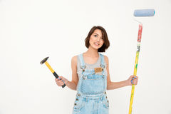 Portrait of young angry beautiful girl, holding hammer and pai Stock Photos