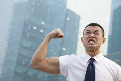Portrait of young angry businessman flexing muscles Royalty Free Stock Photos