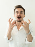 Portrait of young angry man. Angry shouting man at somebody. Screaming man gesturing with hands on white background. Stock Photo