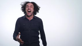 Portrait of young angry man screaming isolated on white background. Close up portrait of young man screaming. Very angry. Casual man screaming stock video footage