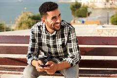 Young arabic man smiling outside with mobile phone. Portrait of young arabic man smiling outside with mobile phone Royalty Free Stock Images