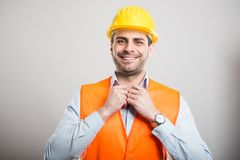 Portrait of young architect arranging his shirt wearing hardhat. And smiling on gray background royalty free stock photos