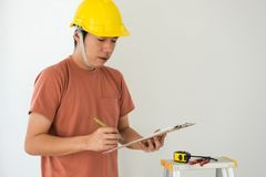 Interior engineer write architect plan on paper. Portrait of Young architect engineer with yellow helmet write plan on paper for interior design of new house Stock Images