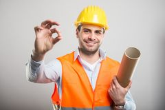 Portrait of young architect holding blueprints making okay gestu. Re and smiling on gray background Stock Images