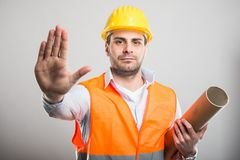 Portrait of young architect holding blueprints making stop gestu. Re on gray background Royalty Free Stock Image