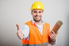 Portrait of young architect holding blueprints offering hand sha. Ke and smiling on gray background with copyspace advertising area Royalty Free Stock Photography