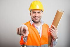 Portrait of young architect holding blueprints pointing camera. And smiling on gray background Stock Image