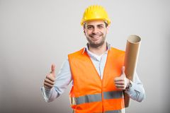 Portrait of young architect holding blueprints showing double li. Ke gesture and smiling on gray background with copyspace advertising area Royalty Free Stock Photos