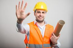 Portrait of young architect holding blueprints showing number fi. Ve and smiling on gray background Royalty Free Stock Photography
